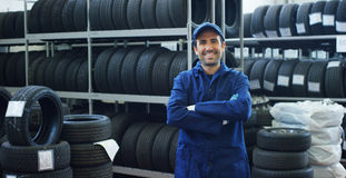 Retrato de un mecánico de coche hermoso joven en un taller del coche, en el fondo del servicio Concepto: reparación de máquinas,  Foto de archivo