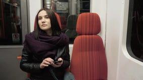 Retrato de un mensaje que mecanografía de la mujer joven en el teléfono móvil en el metro, mujer morena con Smartphone almacen de video