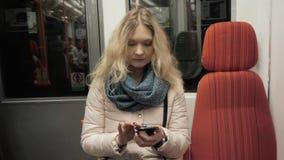 Retrato de un mensaje que mecanografía de la mujer joven en el teléfono móvil en el metro, mujer rubia con Smartphone metrajes