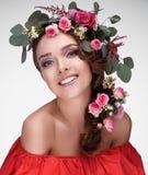 Retrato de un modelo en un vestido rojo con un peinado imponente/un gran trabajo sobre el pelo/el maquillaje oreginalny Foto de archivo libre de regalías