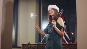 Retrato de un modelo de la muchacha que hace un deseo con las bengalas en sus manos Sombrero de la Navidad Santa Girl Mirada a la almacen de metraje de vídeo
