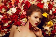 Retrato de un modelo pelirrojo de moda en pétalos color de rosa Foto de archivo libre de regalías