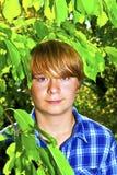 Retrato de un muchacho adolescente con el pelo rubio que se coloca en el jardín Foto de archivo libre de regalías