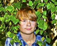 Retrato de un muchacho adolescente con el pelo rubio que se coloca en el jardín Foto de archivo