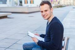 Retrato de un muchacho atractivo del adolescente que se sienta en un banco de madera Imagen de archivo libre de regalías