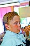 Retrato de un muchacho con el pelo mojado en el peluquero Foto de archivo libre de regalías