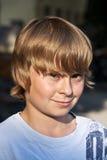Retrato de un muchacho con el pelo rubio largo Foto de archivo libre de regalías