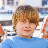 Retrato de un muchacho con el pelo rubio largo que se sienta en un restaurante al aire libre Imágenes de archivo libres de regalías