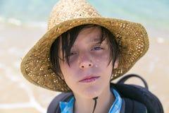 Retrato de un muchacho con el sombrero de paja y la mochila Imagen de archivo libre de regalías