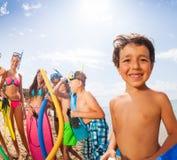Retrato de un muchacho con los amigos en la playa Imágenes de archivo libres de regalías