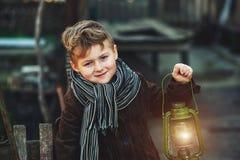 Retrato de un muchacho con una lámpara de keroseno Foto de archivo