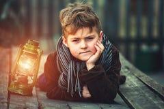 Retrato de un muchacho con una lámpara de keroseno Imagenes de archivo