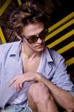 Retrato de un muchacho de moda de relajación en el stai Imagen de archivo