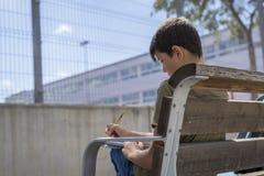 Retrato de un muchacho del adolescente que se sienta haciendo su preparación Imagen de archivo