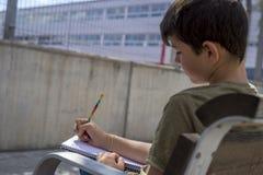 Retrato de un muchacho del adolescente que se sienta haciendo su preparación Fotografía de archivo