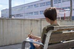 Retrato de un muchacho del adolescente que se sienta haciendo su preparación Fotos de archivo libres de regalías