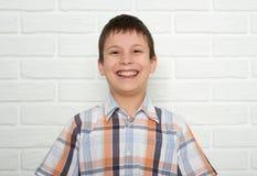 Retrato de un muchacho emocional que se coloca cerca de la pared de ladrillo blanca, vestido en una camisa de tela escocesa Foto de archivo