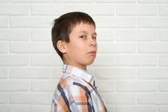 Retrato de un muchacho emocional que se coloca cerca de la pared de ladrillo blanca, vestido en una camisa de tela escocesa Fotos de archivo