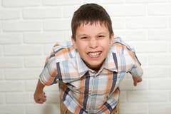 Retrato de un muchacho emocional que se coloca cerca de la pared de ladrillo blanca, vestido en una camisa de tela escocesa Imagen de archivo