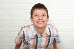 Retrato de un muchacho emocional que se coloca cerca de la pared de ladrillo blanca, vestido en una camisa de tela escocesa Imágenes de archivo libres de regalías
