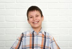 Retrato de un muchacho emocional que se coloca cerca de la pared de ladrillo blanca, vestido en una camisa de tela escocesa Fotos de archivo libres de regalías