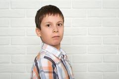 Retrato de un muchacho emocional que se coloca cerca de la pared de ladrillo blanca, vestido en una camisa de tela escocesa Fotografía de archivo libre de regalías
