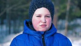 Retrato de un muchacho en un azul abajo de la chaqueta que mira la cámara almacen de metraje de vídeo