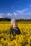 Retrato de un muchacho en un campo amarillo de flores Foto de archivo libre de regalías