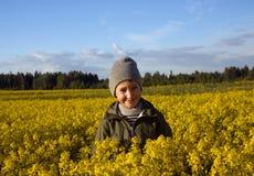 Retrato de un muchacho en un campo amarillo de flores Imagen de archivo