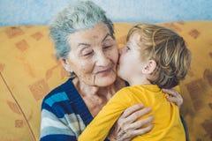 Retrato de un muchacho feliz que besa a la abuela feliz Imagen de archivo libre de regalías