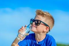 Retrato de un muchacho hermoso sediento en agua potable de las gafas de sol Foto de archivo libre de regalías