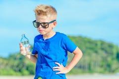 Retrato de un muchacho hermoso sediento en agua potable de las gafas de sol Fotografía de archivo libre de regalías