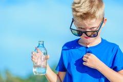 Retrato de un muchacho hermoso sediento en agua potable de las gafas de sol Fotografía de archivo