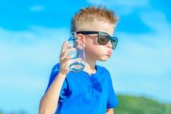 Retrato de un muchacho hermoso sediento en agua potable de las gafas de sol Fotos de archivo