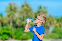 Retrato de un muchacho hermoso sediento en agua potable de las gafas de sol Fotos de archivo libres de regalías
