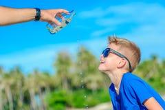 Retrato de un muchacho hermoso sediento en agua potable de las gafas de sol Imágenes de archivo libres de regalías