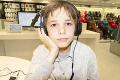 Retrato de un muchacho joven dulce que escucha la música en los auriculares Foto de archivo
