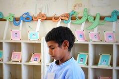 Retrato de un muchacho joven en la biblioteca en la escuela imagen de archivo