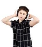 Retrato de un muchacho joven feliz que escucha la música en los auriculares Imágenes de archivo libres de regalías