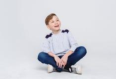 Retrato de un muchacho lindo que se sienta en el piso en el fondo blanco Foto de archivo