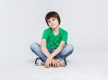 Retrato de un muchacho lindo que se sienta en el piso en el fondo blanco Fotografía de archivo libre de regalías