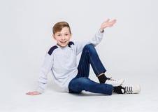 Retrato de un muchacho lindo que se sienta en el piso en el fondo blanco Fotos de archivo libres de regalías