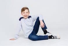 Retrato de un muchacho lindo que se sienta en el piso en el fondo blanco Foto de archivo libre de regalías