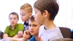 Retrato de un muchacho que piensa en la tarea los pequeños inventores crean los robots con el diseñador, piensan, reflejan, discu almacen de metraje de vídeo
