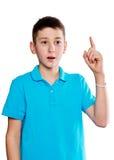 Retrato de un muchacho que señala el finger que muestra las emociones expresivas en un fondo blanco con una camisa azul Fotografía de archivo libre de regalías