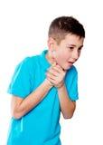 Retrato de un muchacho que señala el finger que muestra las emociones expresivas en un fondo blanco con una camisa azul Foto de archivo