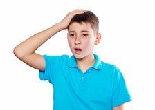Retrato de un muchacho que señala el finger que muestra las emociones expresivas en un fondo blanco con una camisa azul Imágenes de archivo libres de regalías