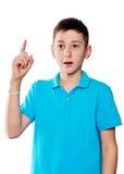 Retrato de un muchacho que señala el finger que muestra las emociones expresivas en un fondo blanco con una camisa azul Fotos de archivo