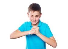 Retrato de un muchacho que señala el finger que muestra las emociones expresivas en un fondo blanco con una camisa azul Imagenes de archivo
