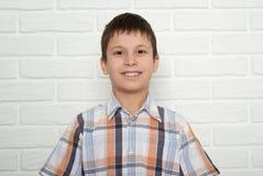 Retrato de un muchacho que se coloca cerca de la pared de ladrillo blanca, vestido en un p Imágenes de archivo libres de regalías